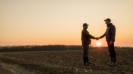 Foto de Two farmers on the field shake hands at sunset. Wide lens shot - Imagen libre de derechos