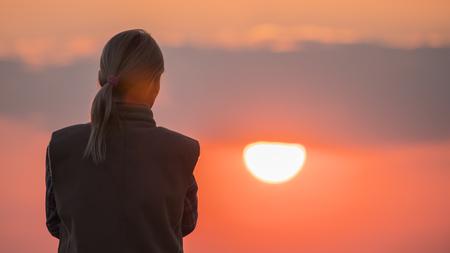 Photo pour A silhouette of a woman looking at a big red sun - image libre de droit