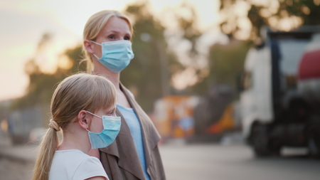 Photo pour A woman with a child in protective masks are standing near a dirty, dusty road in the city - image libre de droit