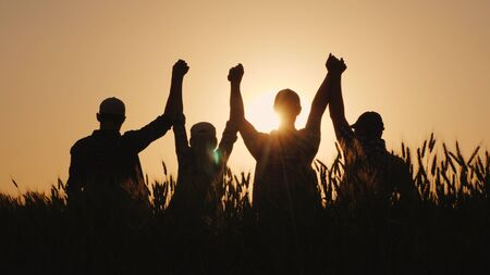 Foto de A group of successful young people hold hands, together they raise their upper hand. Successful team and team building concept. - Imagen libre de derechos