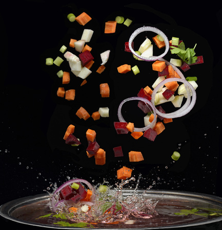Foto de Cut vegetables splash in water soup cooking concept isolated on black background - Imagen libre de derechos
