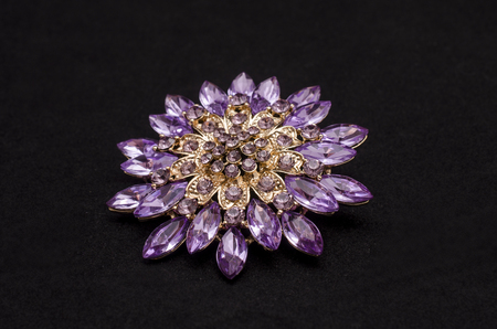 Round brooch with purple diamonds isolated on black
