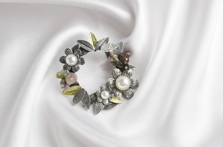 round brooch with flowers and pearls on white silk
