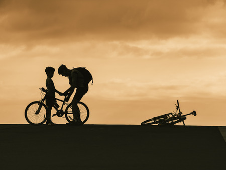 Photo pour Take care Family Silhouette man and kid with bicycle outdoor sport activity Father day Dad and Son - image libre de droit