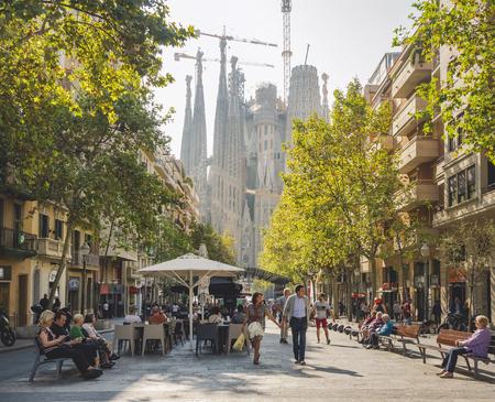 SPAIN, BARCELONA - OCT 21, 2018 : Cafe restaurant Cozy street in Barcelona city People walking Sagrada Familia Architecture landmark