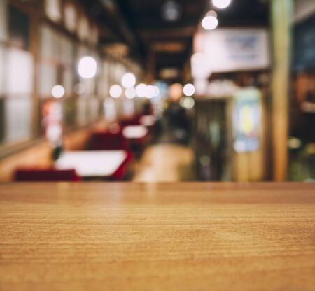 Photo pour Table top wooden counter Blur Cafe restaurant seats interior background - image libre de droit