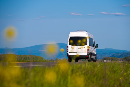 Photo pour Cargo and passenger white van on the road of fuzzy yellow flowers and grass in front and trees, mountains and sky behind - image libre de droit