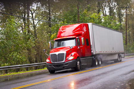 Foto de Big red semi truck shiny and wet from the rain with the reflection of light with a long distance measuring trailer with dust rain under the wheels and reflection of headlights on a wet road passing by green trees. - Imagen libre de derechos