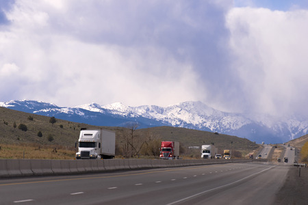 Foto de Modern semi trucks big rigs of various brands and modifications with trailers in the convoy go one by one and transported cargo on the highway with separated lanes running along the mountainous terrain on the background of snowy mountain range and cloudy  - Imagen libre de derechos