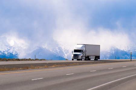 Foto de Big white semi truck with a trailer carrying perishable products refrigerator on a straight highway with separated lanes on the background of snowy mountains drowning in the clouds. - Imagen libre de derechos