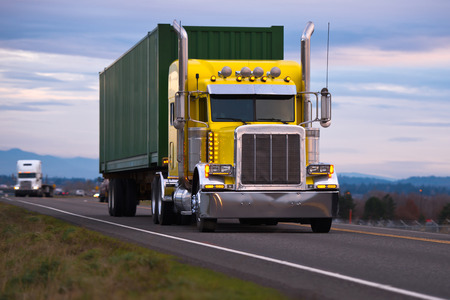 Photo pour Classic American powerful yellow big rig semi truck with high chrome tailpipes powerful headlights and green container local cargo driving on night road against cloudy sky - image libre de droit