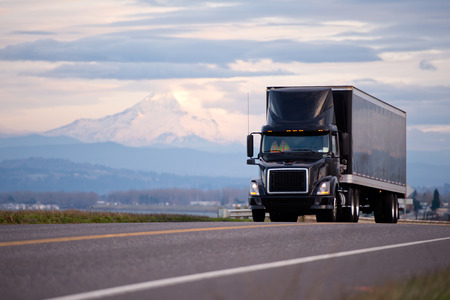 Foto de Stylish black modern powerful semi truck and trailer with a black roof spoiler cockpit makes freight on shipping along the scenic road overlooking the beautiful landscape with snowy mountain and cloudy sky - Imagen libre de derechos