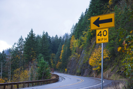 Winding scenic road in the rainy autumn shiny from the rain among the rocks, covered with autumn trees and road sign with the direction arrow and safe travel speed.