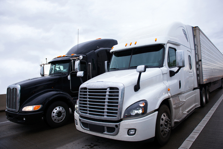Photo pour Two contrasting shiny modern black and white big rigs semi trucks with a trailers and a high sleeper cab for truckers relaxing on truck stop move side by side along the interstate highway carrying commercial goods. - image libre de droit