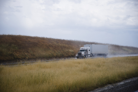Classic American semi truck with a trailer and high tailpipes moves with the load in the rain on the road among the hills with yellow grass, lifting by the wheels clouds of rain dust.の写真素材