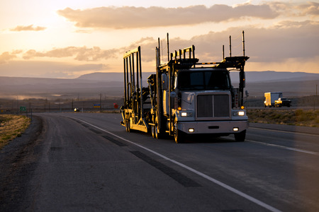 The big rig powerful semi truck with a car hauler trailer for the transporting of cars on the straight road in the Arizona twilight with the last rays of the sun on a trailer rackの素材 [FY31072083141]