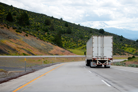 Photo pour A big rig semi truck with a dry van trailer for long haul freight turn on winding dividing highway with green trees on roadside hills - image libre de droit