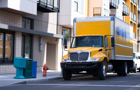 A modern big rig bright yellow local haul medium-duty semi truck with a day cab and a dry van box trailer moves along the street road of an urban city to transport a loaded trailer to the destination apartment