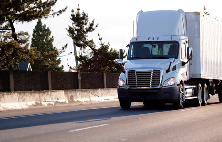 A modern big rig bright white local haul medium-duty semi truck with a day cab with roof spoiler for better aerodynamic and a dry van semi trailer moves along the highway road to transport a loaded trailer to the destination warehouse