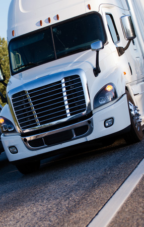 Modern model of powerful heavy bonnet classic white big rig semi truck with slim shape and dry van semi trailer for boxed cargo driving by highway in city limit area delivering loaded cargo to destination warehouse