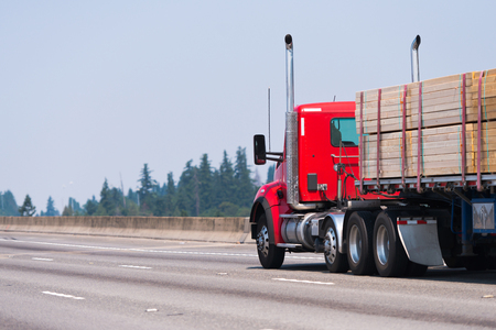Professional American big rig high cab powerful red semi truck with vertical exhaust pipes and flat bed semi trailer transporting lumber cargo and running alone on the highway road with green treesの素材 [FY31086790833]