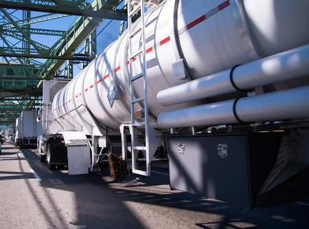 Big rig semi truck with tank semi trailer for the transport of chemical and flammable substances and liquids moves through the bridge in convoy traffic with other vehicles