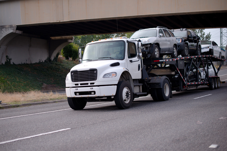 A white medium-duty car hauler semi truck transports vehicles on a special two-tier semi trailer along the highway passing under a bridge crossing the road