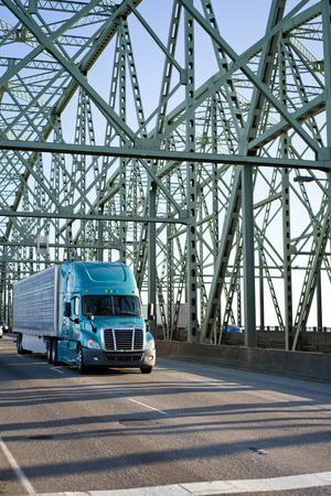 Big rig long haul modern blue semi truck with refrigerator semi trailer carry perishable food cargo and driving on the Interstate Columbia River bridge with section trusses arches