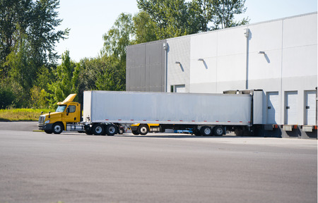 Photo for A huge number of big rig semi trucks are loaded and unloaded in the docks of huge warehouses, detaches semi trailers, attaching already loaded ones, and again the truckers kings of roads are set off - Royalty Free Image