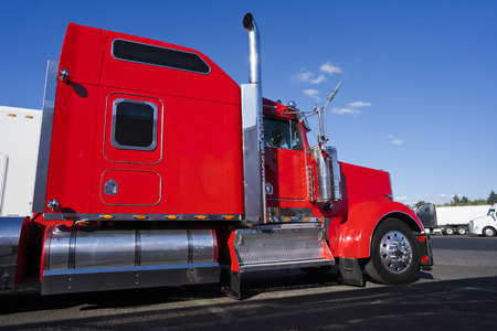 Profile of bright red big rig classic American semi truck with chrome parts and flat bed semi trailer carry commercial cargo fixed by slings stand on truck stop beside another semi trucks
