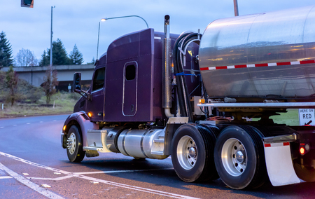 Big rig purple American bonnet powerful semi truck transporting liquid in long shiny cylindrical tank semi trailer turning on the entering highway evening twilight slippery wet road