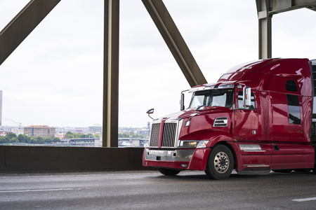 Photo pour Bright pearl red modern big rig semi truck with geometric shape and high cabin for long haul flights driving on the wide bridge transporting commercial cargo in refrigerated semi trailer - image libre de droit