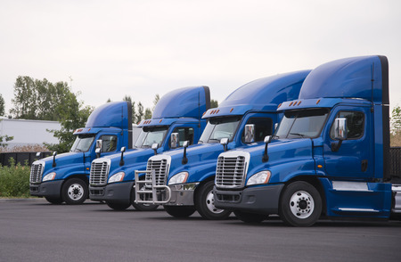 Foto de Side view of the blue big rigs semi trucks tractors with high roof spoiler for better aerodynamic flow stand in row without semi trailers on the parking lot and waiting for loading cargo for delivery - Imagen libre de derechos