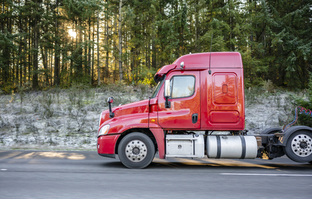 Freight transport by semi trucks in America - the main type of logistics. Red big rig semi truck with cargo on flat bed semi trailers running on highway with winter frosty trees with sun