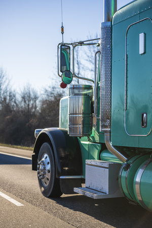 Photo pour Part of big rig bright green classic American semi truck with extended cab for long haul routs transporting semi trailer driving on the straight highway in sunny day - image libre de droit