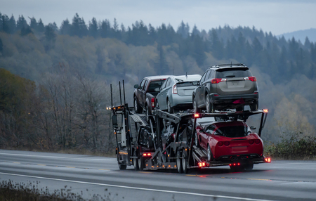 Photo pour Car transportation by big rig semi truck allows all dealerships to ensure uninterrupted sale of new and used cars ensuring consumer demand in any state of America. Trucks carry out the main freight - image libre de droit