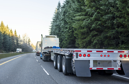 Photo pour Big rig long haul powerful semi truck with empty light weight aluminum flat bed semi trailer running on the winter road in convoy with another semi trucks and evergreen trees - image libre de droit