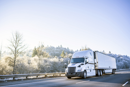 Photo pour Big rig white technological improved long haul semi truck with refrigerated semi trailer for transportation of perishable and frozen food going on the winter road with snowy frost trees on the hill - image libre de droit
