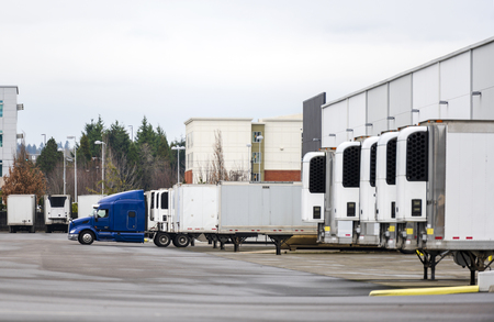 Photo pour Big rig blue semi truck and refrigerated semi trailers standing in row in warehouse dock for loading and unloading commercial cargo and continuing go to the destination according to schedule - image libre de droit