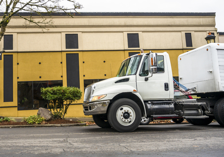 Middle-duty class day cab white rig semi truck for local transporting and delivery goods with low semi trailer driving on the small city street with buildings on the background