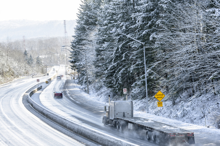 Photo pour Big rig long haul semi truck tractor transporting empty semi trailer going to warehouse for loading cargo running on wet glossy road with water from melting snow and winter snowy trees on the hill - image libre de droit