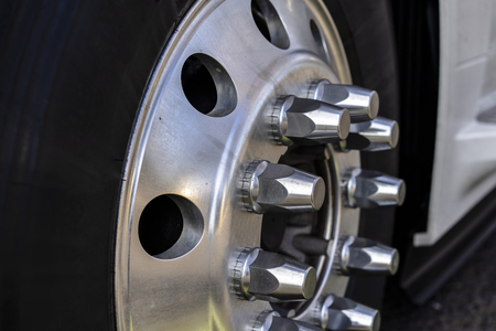 The wheel of long haul American logistic freight leader transportation big rig semi truck with tire aluminum rim and chrome mounting bolts mounted on the truck axle