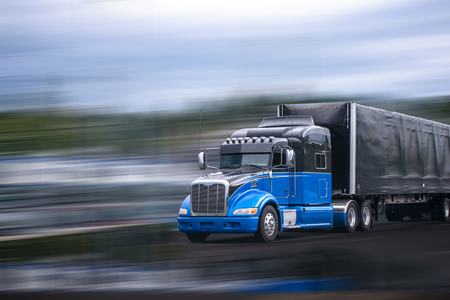 Stylish black and blue big rig long haul semi truck with aerodynamic spoilers transporting commercial cargo in full size black covered semi trailer moving on wide multiline divided highway road