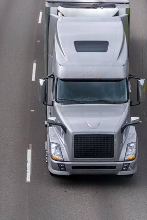 Classic modern design stylish gray big rig bonnet long haul semi truck transporting frozen and chilled cargo in full size refrigerated semi trailer moving on wide multiline divided highway road