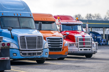Foto de Different bonnet makes and models of professional big rigs semi trucks with commercial cargo on semi trailers standing in row on the industrial truck stop parking lot waiting for unloading - Imagen libre de derechos