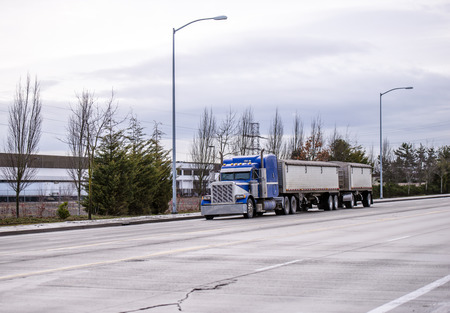 Blue classic big rig American semi truck with vertical exhaust pipes and sleeping compartment running on wide road in industrial area transporting two covered bulk semi trailer with commercial cargo