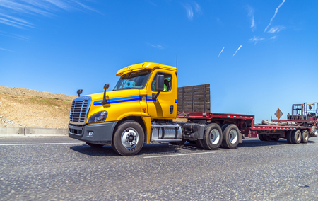 Photo pour Yellow big rig day cab semi truck for local regional delivery with empty step down semi trailer and forklift mounted at the end of the trailer running on the road to warehouse for loading - image libre de droit