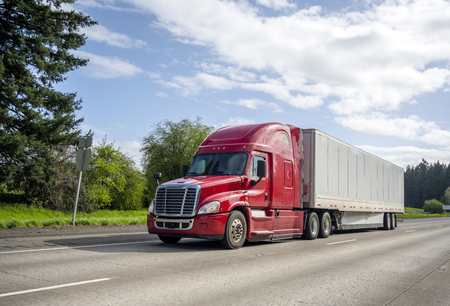 Photo for Red big rig popular professional reliable bonnet long haul semi truck transporting commercial cargo in dry van semi trailer moving on the straight wide highway with green trees on the background - Royalty Free Image