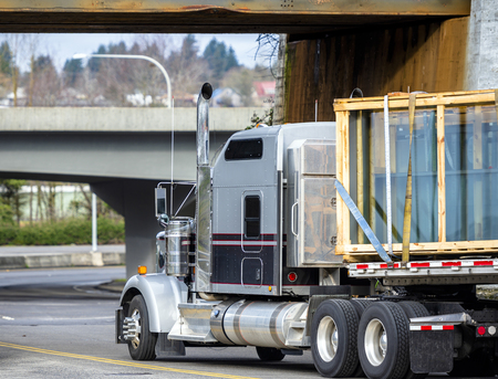Big rig gray and black classic long haul semi truck transporting windows glass sheets in wood boxes fastened on flat bed semi trailer turning under low rusty metal bridge going to highway entrance