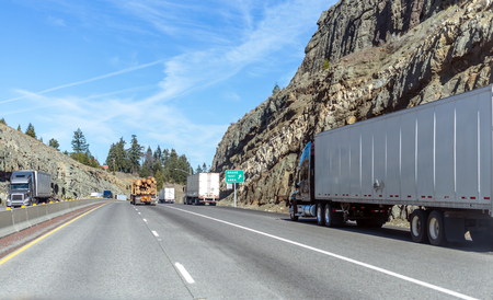 Big rigs American freight semi trucks with loaded semi trailers running on mountain pass in California are moving along all lanes of the highway including along the side of the road in the brake lane